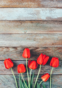 Boeket van rode tulpen op lichtblauwe houten retro grunge met copyspace.
