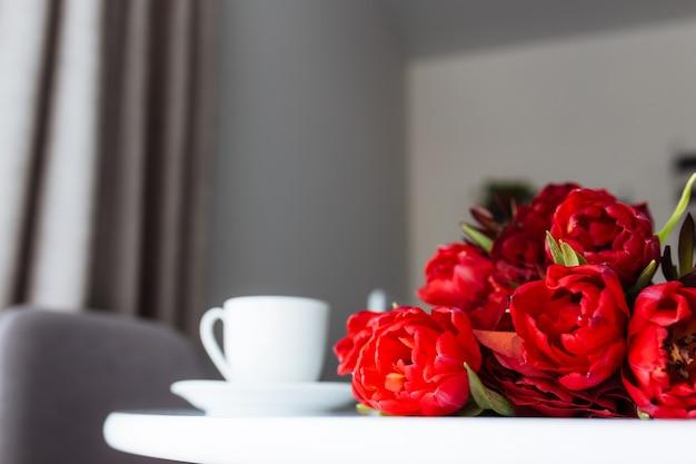 Boeket van rode tulpen op tafel en witte koffiekopje. wenskaart concept