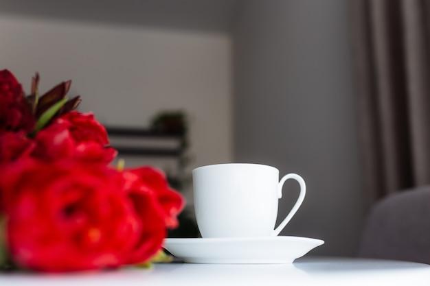 Boeket van rode tulpen op tafel en witte koffiekopje