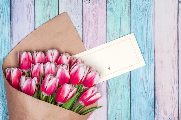 Boeket van rode tulpen voor de dag van vakantiemoedelen en de dag van de valentijnskaart op de achtergrond van houten raad.