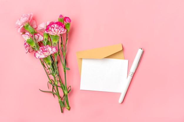 Boeket van roze anjer bloem envelop, pen en wit notitie papier op roze achtergrond