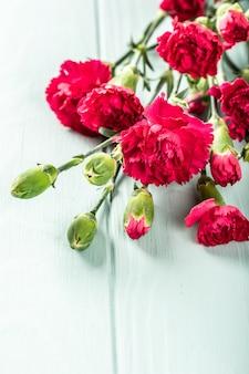 Boeket van roze anjer op licht turkoois houten oppervlak. wenskaart met kopie ruimte