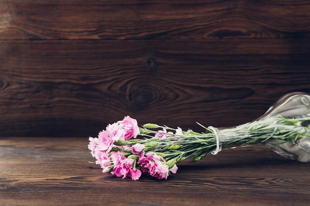 Boeket van roze anjerbloemen in vaas op hout. lege ruimte voor tekst