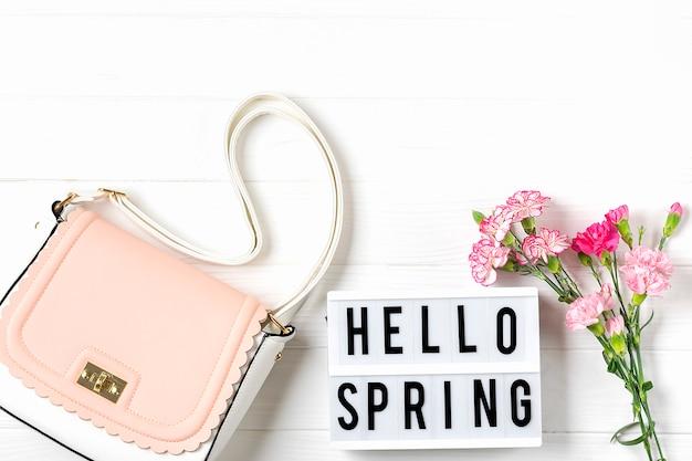Boeket van roze anjers bloemen, lichtbak met tekst hallo lente, vrouw handtas op witte houten achtergrond