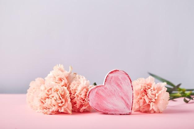 Boeket van roze anjers en decoratief hartontwerpconcept van vakantiegroet met anjerbo...