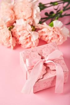 Boeket van roze anjers en roze geschenkdoos ontwerpconcept van vakantiegroet met anjerboeke...