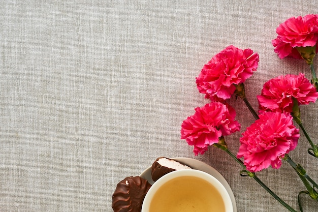 Boeket van roze anjers met thee op grijze stof