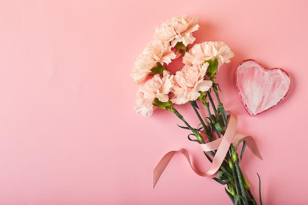 Boeket van roze anjers ontwerpconcept van vakantie groet met anjer boeket op roze tafel b...