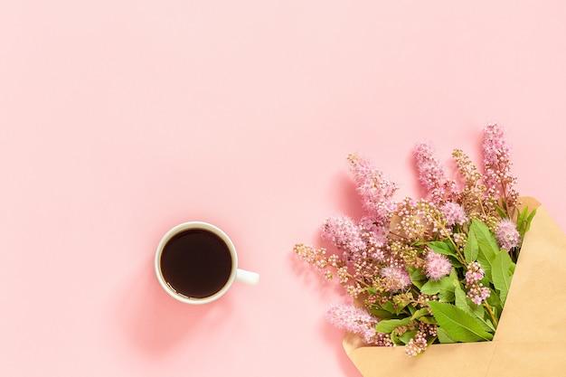 Boeket van roze bloemen in envelop, kopje koffie en een witte lege kaart voor tekst op roze achtergrond