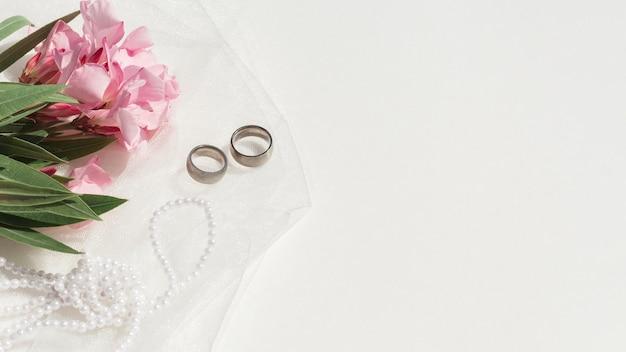 Boeket van roze bloemen naast bruiloft arrangement met kopie ruimte