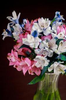 Boeket van roze en blauwe alstroemeria bloemen in glazen vaas.