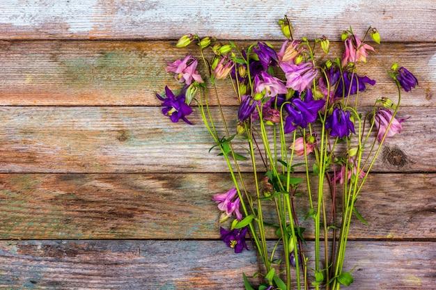 Boeket van roze en blauwe aquilegia bloemen op een retro houten achtergrond met een kopie ruimte bovenaanzicht copy