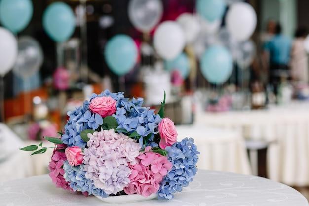 Boeket van roze en blauwe hortensia's en rozen ligt op een witte tafel