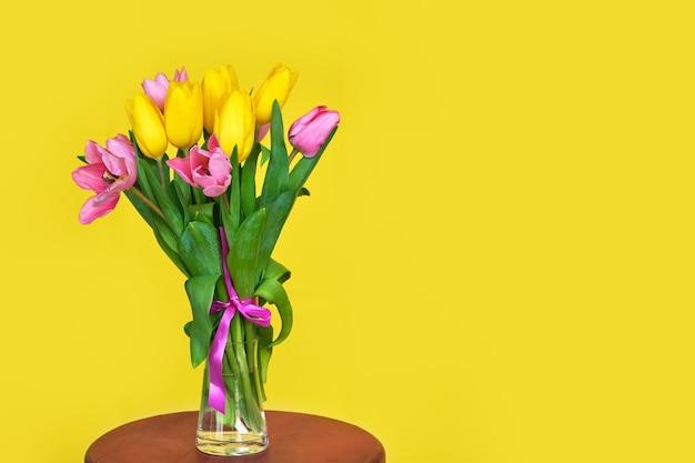 Boeket van roze en gele tulpen op gele ondergrond