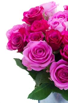 Boeket van roze en magenta verse bloeiende rozen in kan close-up geïsoleerd op een witte achtergrond