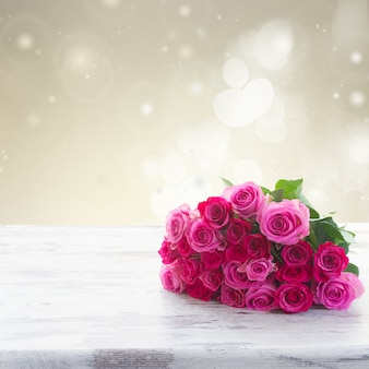 Boeket van roze en magenta verse rozen op houten tafelgrens geïsoleerd op een witte achtergrond