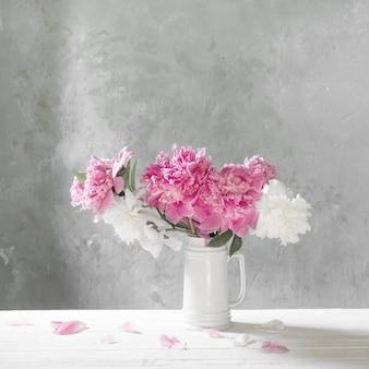 Boeket van roze en witte pioenen op oude muur als achtergrond