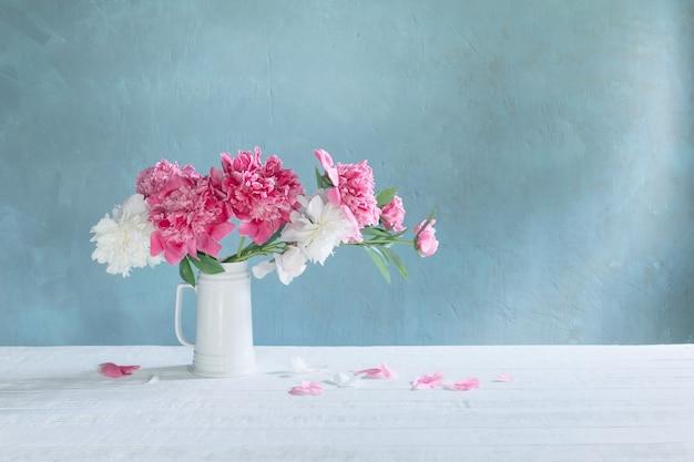 Boeket van roze en witte pioenrozen op de muur