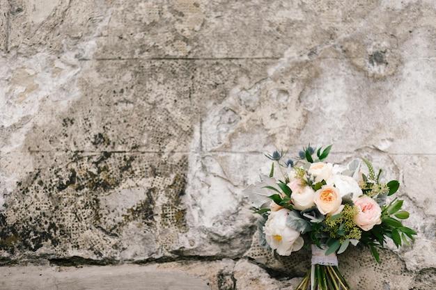 Boeket van roze en witte poenies ligt vóór een concrete muur