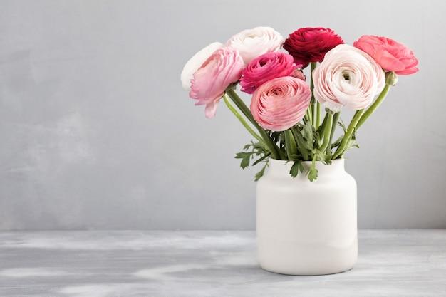 Boeket van roze en witte ranunculus bloemen over de grijze muur