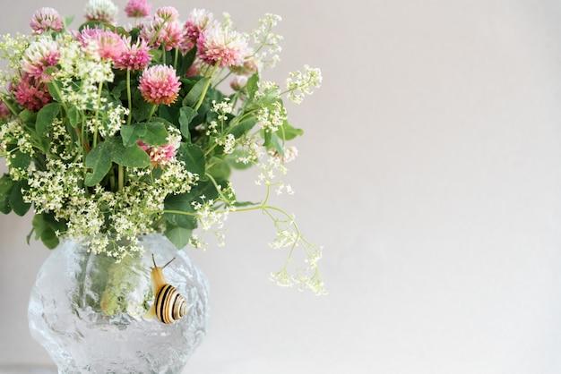 Boeket van roze klaverbloemen in ronde vaas met schattige kruipende slak