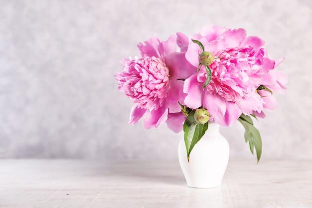 Boeket van roze pioenrozen in een vaas op een houten tafel. gift valentijnsdag.
