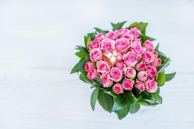 Boeket van roze rozen en trouwringen. ruimte kopiëren. het concept