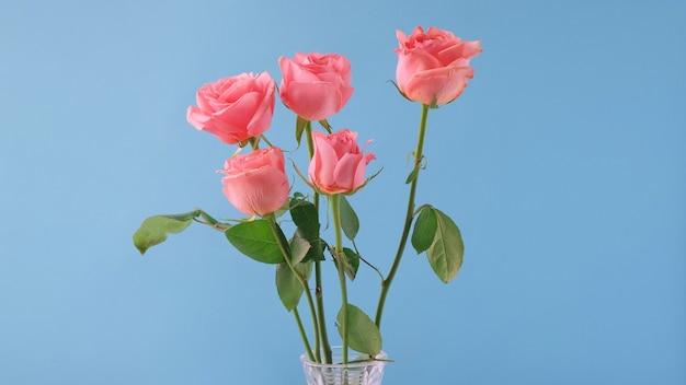 Boeket van roze rozen geïsoleerd op blauw