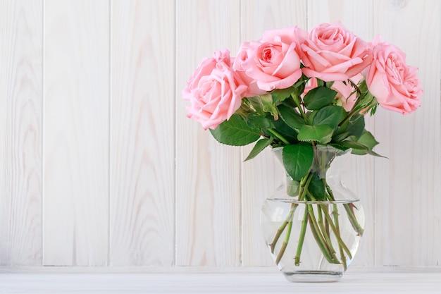 Boeket van roze rozen in een glazen vaas, florale achtergrond.