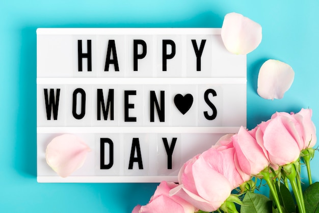 Boeket van roze rozen op een blauwe achtergrond en lightbox met citaat gelukkige womens dag