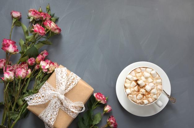 Boeket van roze struikrozen, vrouwelijk geschenk en kopje koffie