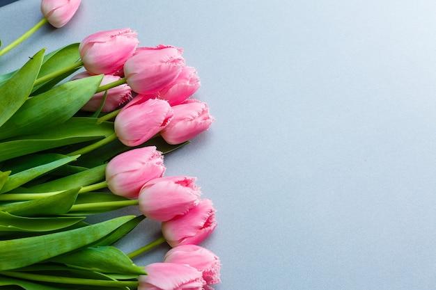 Boeket van roze tulp bloemen op grijze achtergrond plat lag.