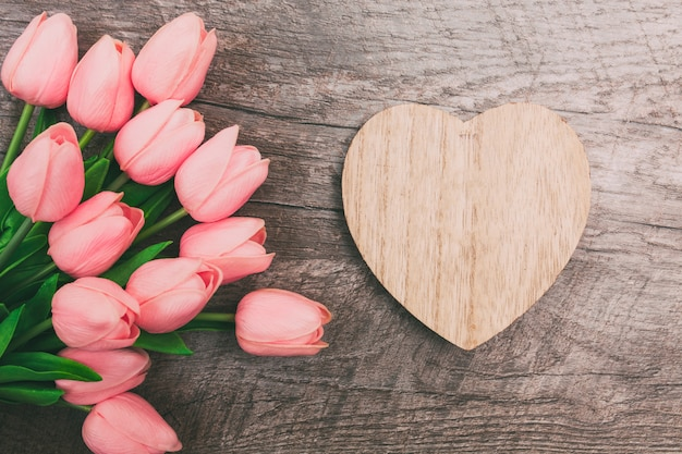 Boeket van roze tulpen en een valentijn in de vorm van een hart van hout, op een houten achtergrond