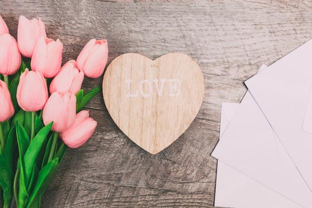 Boeket van roze tulpen en witte lege enveloppen, op houten achtergrond