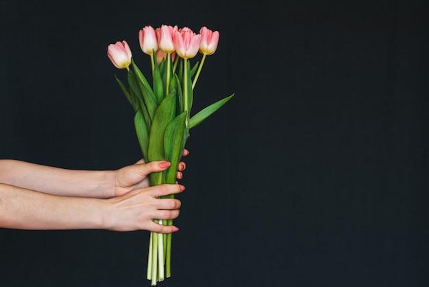 Boeket van roze tulpen in de hand van een vrouw