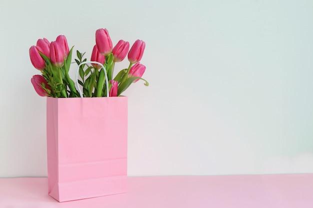 Boeket van roze tulpen in een roze papieren zak