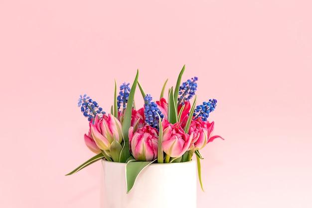 Boeket van roze tulpen in een witte vaas op een roze achtergrond. detailopname. hallo lente concept