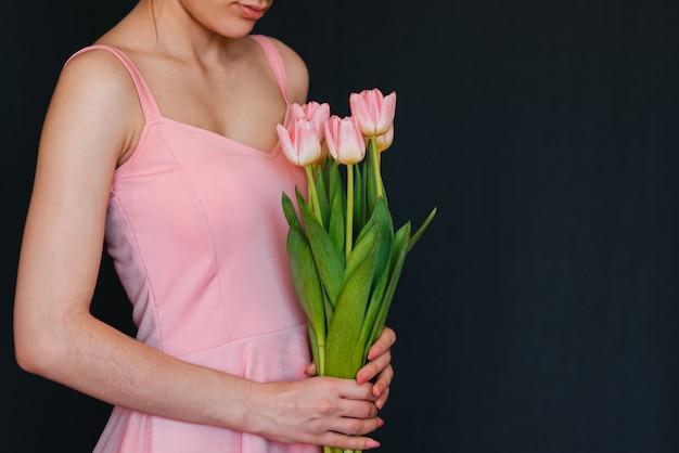 Boeket van roze tulpen in handen van vrouwen