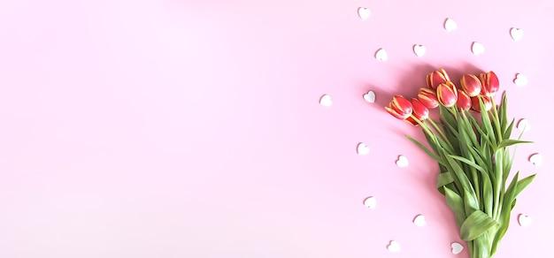 Boeket van roze tulpen met decoratieve hart hagelslag op zachte pastel lichte achtergrond. bovenaanzicht. valentijnsdag feestelijke achtergrond.