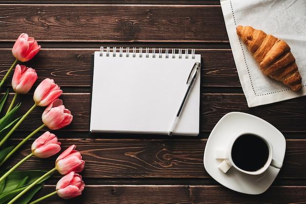 Boeket van roze tulpen met een kopje koffie en een croissant