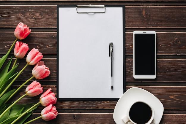 Boeket van roze tulpen met een kopje koffie en een smartphone op een houten tafel