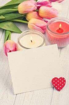 Boeket van roze tulpen met lege kaart en hart