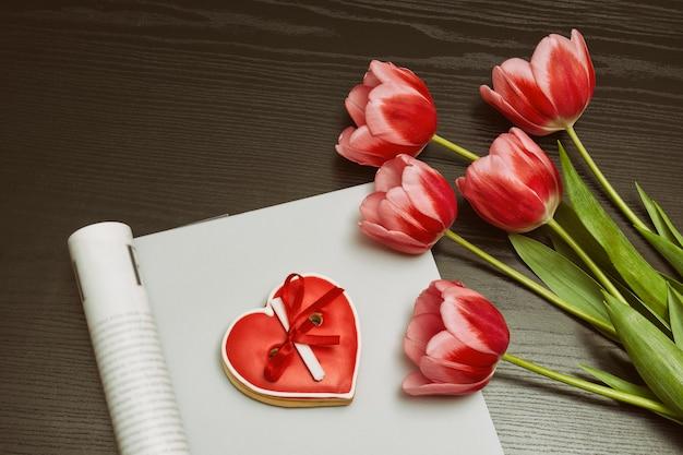 Boeket van roze tulpen, rode hartvormige koekjes met een notitie, leeg tijdschrift