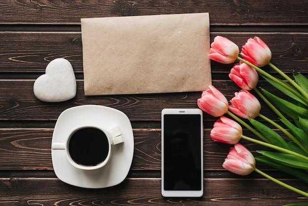 Boeket van roze tulpenbloemen met een kopje koffie en een smartphone voor het ontbijt in de ochtend