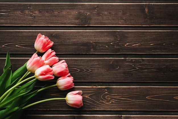 Boeket van roze tulpenbloemen op een bruine houten tafel.