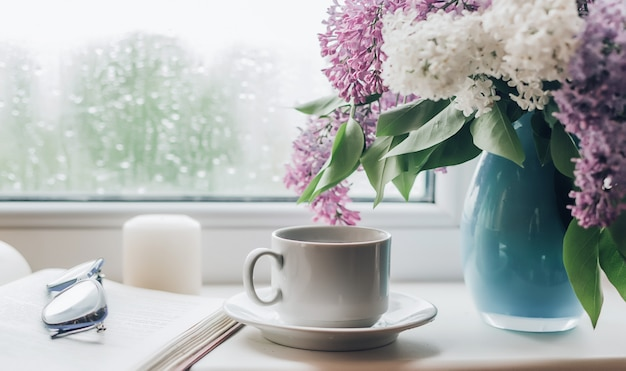 Boeket van seringen in een vaas en kopje koffie