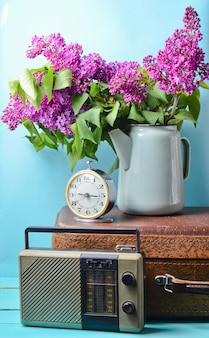 Boeket van seringen in geëmailleerde ketel op antieke koffer, vintage radio, wekker op blauwe muur