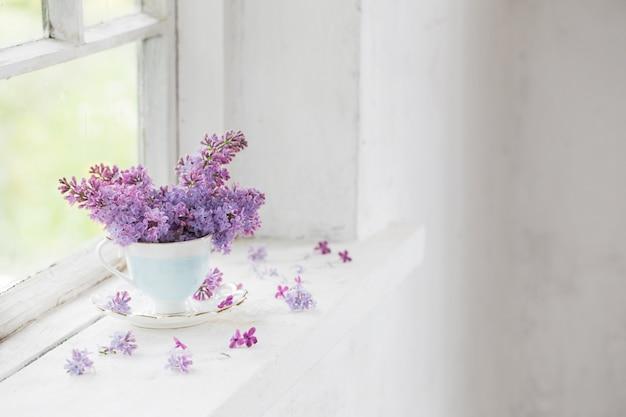 Boeket van seringen in keramische cup op oude witte vensterbank