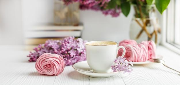 Boeket van seringen, kopje koffie, zelfgemaakte marshmallow en boeken. romantische lentemorgen.