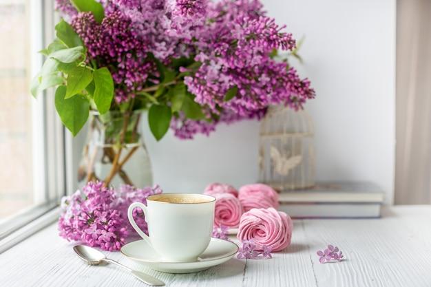 Boeket van seringen, kopje koffie, zelfgemaakte marshmallow en stapel boeken. romantische lentemorgen.